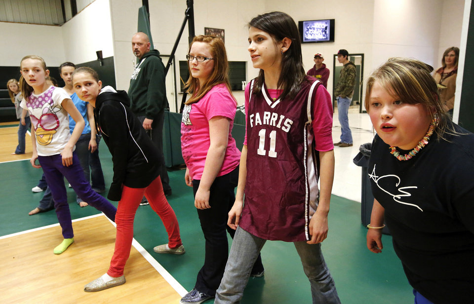 Photo - Former Farris student Druid Gibson wears a jersey from her old school while participating in a game of dodgeball during a P.E. class in the Lane School gymnasium on her first day of classes in her new school. About 50 students transferred to Lane Public School after their former school, Farris School, was annexed by Lane in Atoka County.   Photo taken  March 1, 2013. Photo by Jim Beckel, The Oklahoman