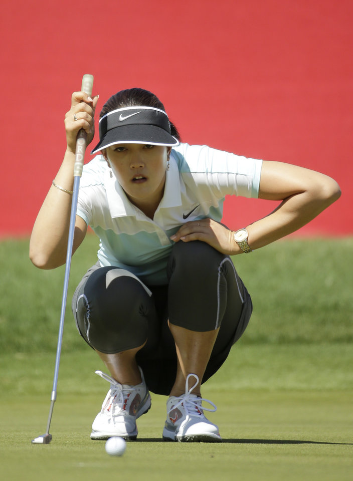 Photo - Michelle Wie lines up a putt on the ninth hole during the first round at the Kraft Nabisco Championship golf tournament on Thursday, April 3, 2014, in Rancho Mirage, Calif. (AP Photo/Chris Carlson)