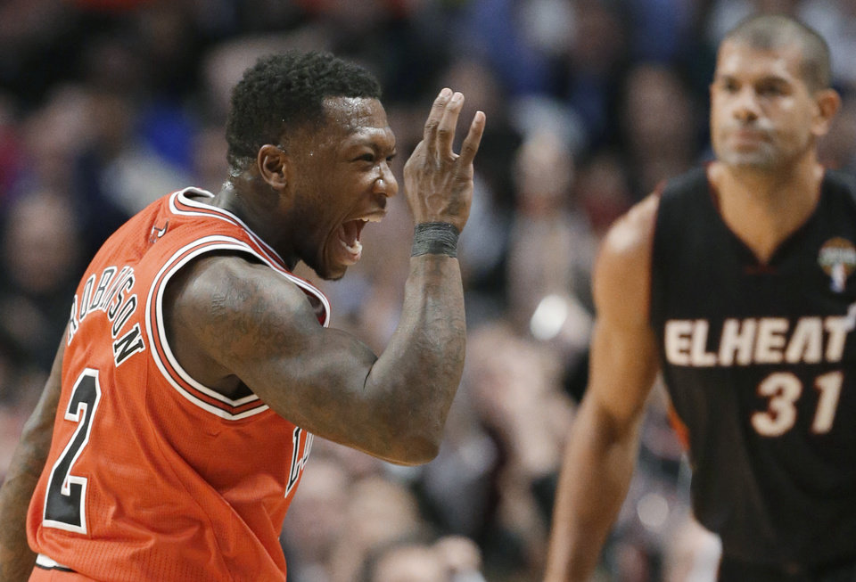 Photo - Chicago Bulls guard Nate Robinson, left, celebrates a 3-point shot, as Miami Heat forward Shane Battier watches during the first half of an NBA basketball game in Chicago on Wednesday, March 27, 2013. (AP Photo/Nam Y. Huh)
