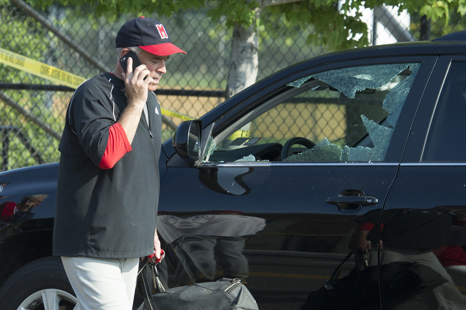 Photo - Rep. Brad Wenstrup, R-Ohio talks on the phone as he walks past a damaged vehicle in Alexandria, Va., Wednesday, June 14, 2017, after a shooting where House Majority Whip Steve Scalise of La., and others, were shot during a Congressional baseball practice. (AP Photo/Cliff Owen)
