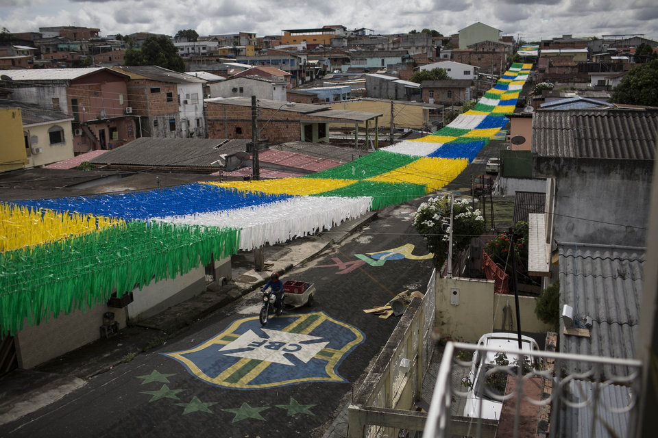 Photo - In this May 21, 2014 photo, a man rides his motorbike under a canopy of ribbons through a street decorated in honor of the upcoming 2014 World Cup, in Manaus, Brazil. While the forest fauna is largely absent from the metropolis itself, nature makes itself felt in the hothouse climate and the blooms of mold that envelop the low-slung concrete buildings. Humidity hovers around 80 percent year-round. (AP Photo/Felipe Dana)