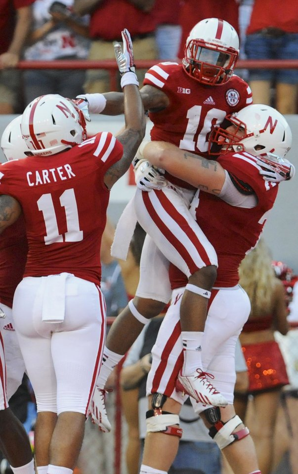 Photo - Nebraska offensive linesman Mike Moudy, right, and Nebraska tight end Cethan Carter (11) celebrate with Nebraska wide receiver Jamal Turner (10), after Turner scored in the first half of an NCAA college football game against Wyoming in Lincoln, Neb., Saturday, Aug. 31, 2013. (AP Photo/Dave Weaver)
