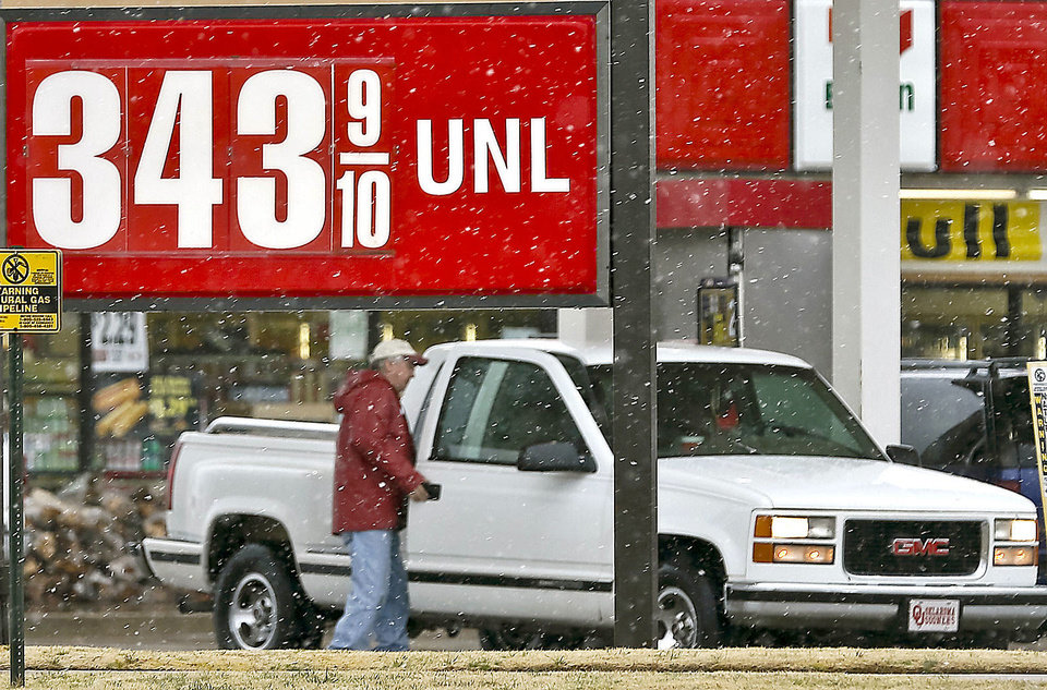 Photo - Drivers line up at gasoline pumps as snow falls Monday in Oklahoma City. Photo by Chris Landsberger, The Oklahoman
