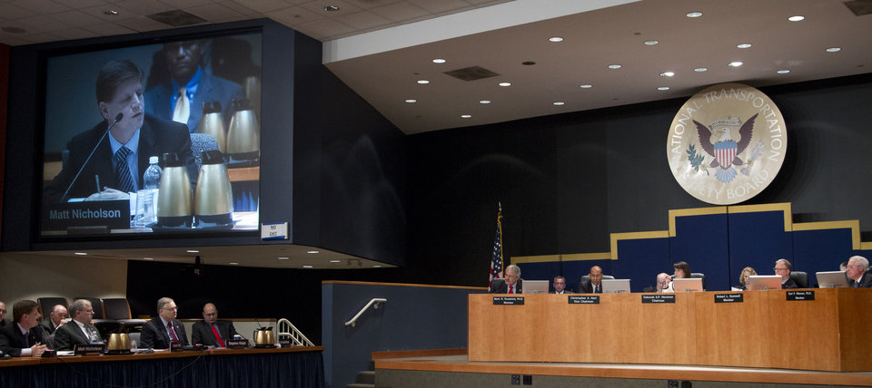 Photo -   National Transportation Safety Board (NTSB) Investigator-In-Charge Matt Nicholson is projected on a monitor as he testify during a NTSB meeting in Washington Tuesday, July 10, 2012, presided by NTSB Chair Deborah Hersman, center right panel, to determine a cause of a pipeline rupture in 2010 that dumped more than 800,000 gallons of oil into a southwestern Michigan river. (AP Photo/Manuel Balce Ceneta)