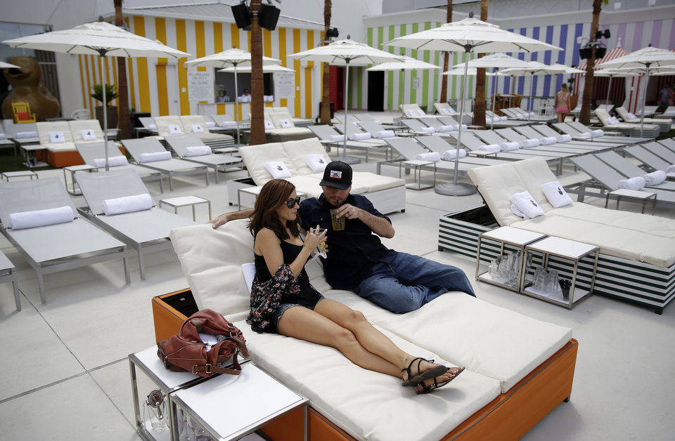Photo - In this photo taken on Aug. 20, 2014, Amelia Perez, left, and Fabian Perez lounge by the pool at the SLS Las Vegas in Las Vegas. The hotel and casino, formally known as the Sahara, has gone through extensive renovations is scheduled to open this weekend. (AP Photo/John Locher)