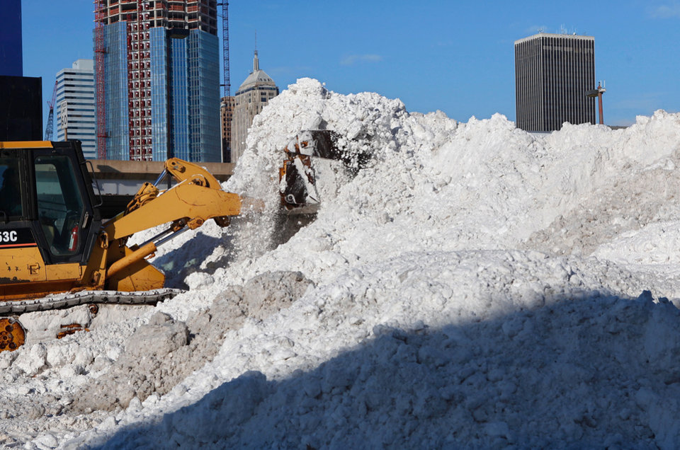 Photo - With downtown buildings as a backdrop, a city worker operates a front end loader to push snow higher after another load of snow was brought in Wednesday afternoon.  A parade of snow-laden dump trucks made their way to vacant lots just south of the downtown area to unload snow that had been cleared from downtown streets throughout the day. A large mountain of snow was created in a lot at SW 3 and Harvey. By late afternoon, when snow filled this area, the trucks were diverted to a parking lot at SW 3 and Hudson where drivers arrived about every three minutes to dump their load of snow. A second winter storm in a week produced about 6 inches of snow in the Oklahoma City area Wednesday morning, Feb. 9, 2011.   Photo by Jim Beckel, The Oklahoman