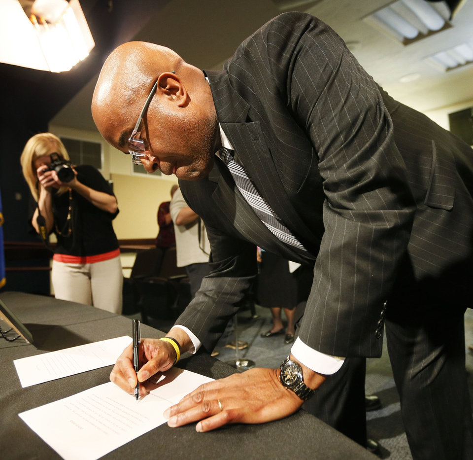 Photo - Ward 3 Edmond Councilman Darrell A. Davis signs the oath of office. PHOTO BY NATE BILLINGS, THE OKLAHOMAN.  NATE BILLINGS - THE OKLAHOMAN