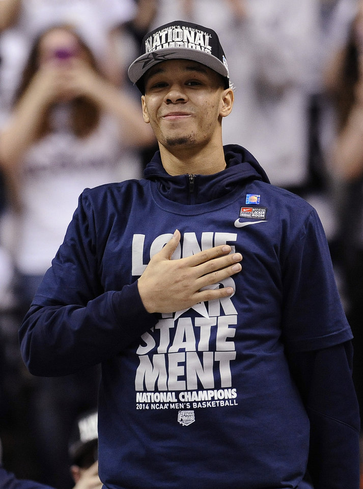 Photo - Connecticut's Shabazz Napier places his hand over his heart as he is cheered on by fans at a pep rally celebrating the program's fourth national championship, Tuesday, April 8, 2014, in Storrs, Conn. (AP Photo/Jessica Hill)