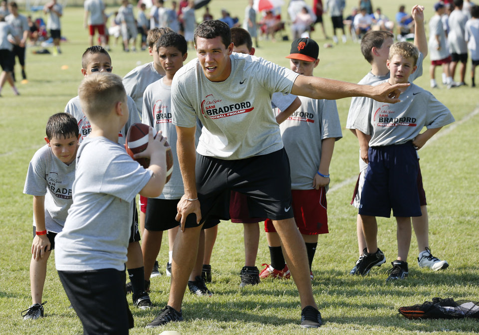 Sam Bradford works with campers during his football camp on the campus of the University of Oklahoma on Wednesday, July 11, 2012, in Norman, Okla.  Photo by Steve Sisney, The Oklahoman
