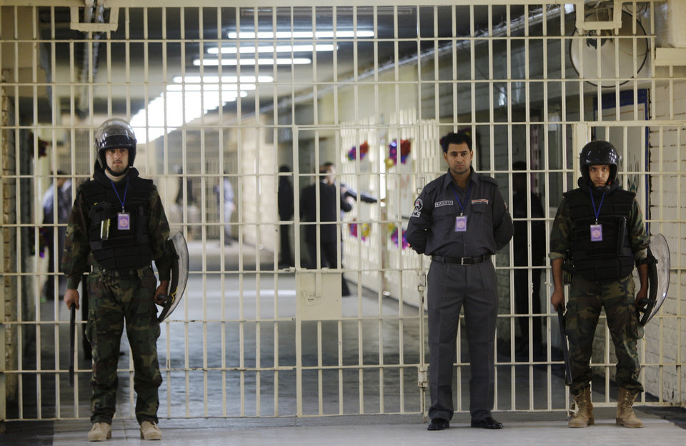 Photo - FILE - In this Feb. 21, 2009 file photo, guards stand at a cell block at the renovated Abu Ghraib prison, now renamed Baghdad Central Prison and run by Iraqis in Baghdad, Iraq. Late-night jailbreak attempts at two major prisons outside Baghdad have killed dozens, including at least 25 members of Iraq's security forces who battled militants armed with car bombs, mortars and machine guns, officials said Monday. (AP Photo/Karim Kadim, File)