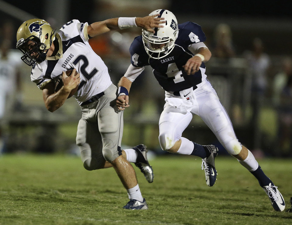 Heritage Hall's TJ Schallner (22) runs from Casady's Drew Cook (4) during a game at Casady High School in The Village, Okla., Thursday, Aug. 30, 2012.  Photo by Garett Fisbeck, The Oklahoman