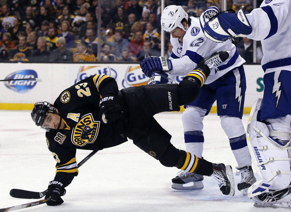 Photo - Tampa Bay Lightning left wing Ryan Malone (12) dumps Boston Bruins center Chris Kelly (23) to the ice in front of goalie Anders Lindback during the second period of an NHL hockey game in Boston Monday, Nov. 11, 2013. The Bruins won 3-0. (AP Photo/Elise Amendola)