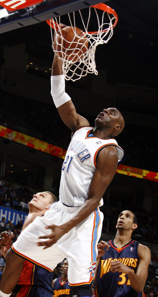 Photo - Damien Wilkins of Oklahoma City dunks the ball as Andris Biedrins, left, and Brandan Wright of Golden State look on in the first half during the NBA basketball game between the Golden State Warriors and the Oklahoma City Thunder at the Ford Center in Oklahoma City, Monday, December 8, 2008. BY NATE BILLINGS, THE OKLAHOMAN