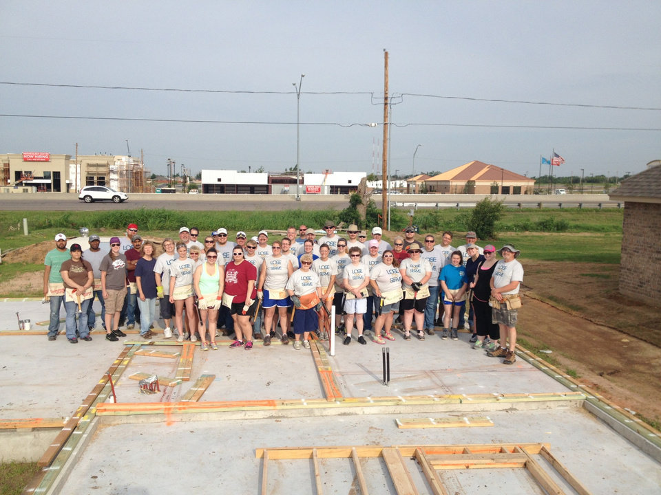 Photo -  Members of Shartel Church of God who participated in the Lose to Serve fitness challenge pose for a photo on the concrete foundation for Karissa Smith's new home. Photo provided