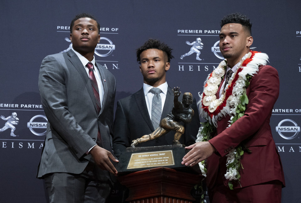 Photo - Heisman Trophy finalists, from left, Dwayne Haskins, from Ohio State; Kyler Murray, from Oklahoma; and Tua Tagovailoa, from Alabama, pose with the trophy during a media event Saturday, Dec. 8, 2018, in New York. (AP Photo/Craig Ruttle)