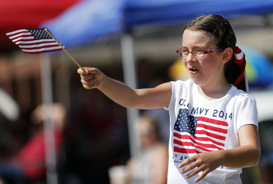 Photo - Chloe Sodowsky, 7, waves an American flag during the Edmond LibertyFest Parade in downtown Edmond, Okla., on Independence Day, Friday, July 4, 2014. Photo by Nate Billings, The Oklahoman