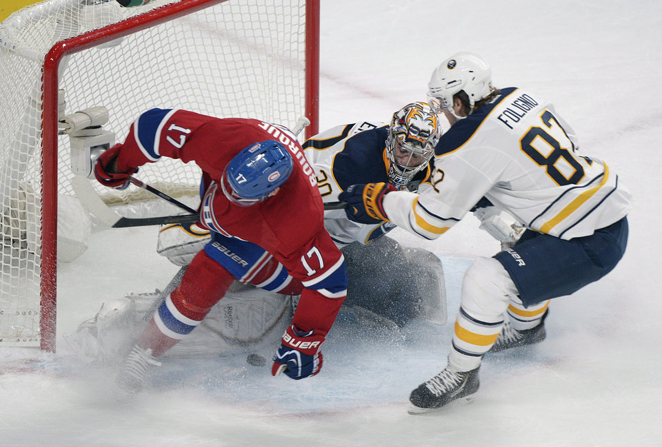 Photo - Montreal Canadiens' Rene Bourque slides in on Buffalo Sabres' goaltender Ryan Miller, centerre, and Marcus Foligno (82) during first period NHL hockey action in Montreal, Saturday, Feb. 2, 2013. (AP Photo/The Canadian Press, Graham Hughes)