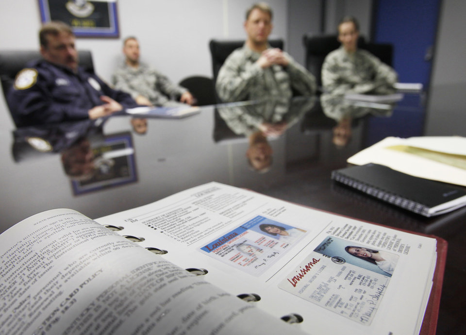 Photo - Vance Air Force Base officials discuss security at the base in Enid, Friday, February 5, 2010. In the foreground is a book used to spot fake IDs. Goes with a Randy Ellis story on security at Vance Air Force Base. Photo by David McDaniel, The Oklahoman ORG XMIT: KOD