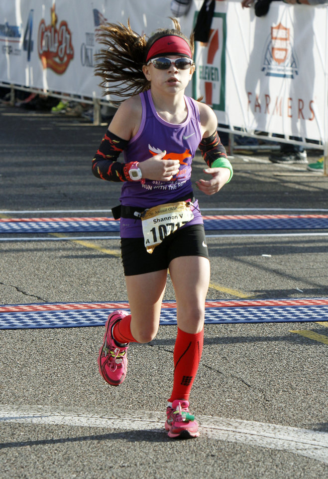 Photo - Ten-year-old Shannon Varenhorst finishes the half-marathon of the Oklahoma City Memorial Marathon in Oklahoma City, Sunday, April 28, 2013,  By Paul Hellstern, The Oklahoman