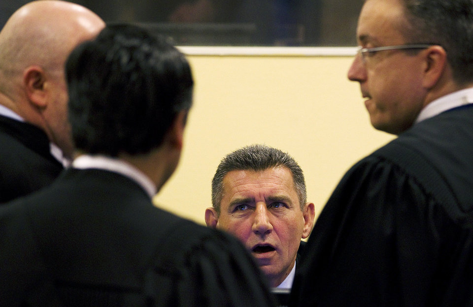 FILE This Friday, April 15, 2011 shows former Croatian Army General Ante Gotovina, center, talks to his defense team, prior to his verdict in the courtroom of the Yugoslav war crimes tribunal in The Hague, Netherlands. Thousands of Croatians are attending Masses and candlelight vigils for their hero, Gen. Ante Gotovina, as they anxiously await the outcome of his appeal Friday Nov. 15, 2012 against a war crimes verdict at a U.N. tribunal. Gotovina and Gen. Mladen Markac were last year sentenced to 24 and 18 years in jail respectively for war crimes against minority Serbs during a 1995 military offensive that retook the land held by the rebels. Some 600 Serbs were killed and more than 200,000 were driven from their homes during the operation. (AP Photo/Jerry Lampen, Pool)