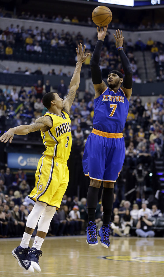 Photo - New York Knicks forward Carmelo Anthony, right, shoots over Indiana Pacers guard George Hill during the first half of an NBA basketball game in Indianapolis, Thursday, Jan. 16, 2014. (AP Photo/Michael Conroy)