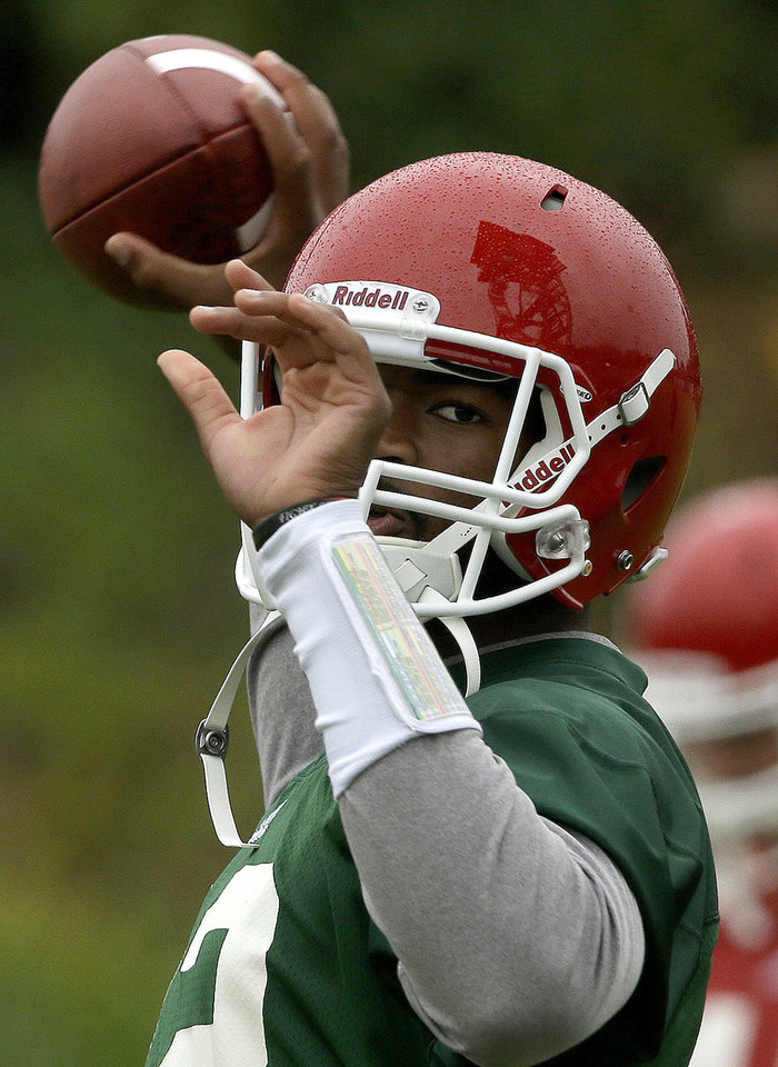 Photo - North Carolina State quarterback Jacoby Brissett looks to pass during the team's first NCAA college football practice of the season in Raleigh, N.C., Saturday, Aug. 2, 2014. (AP Photo/Gerry Broome)