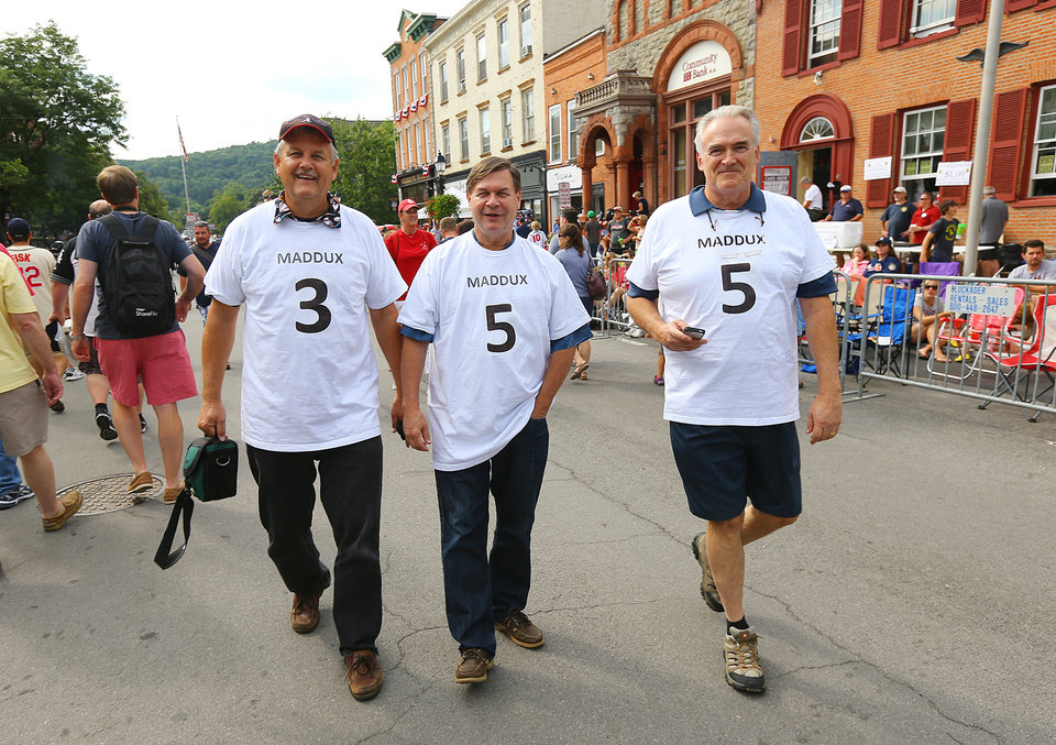 Photo - Tom Williamson, Kevin McIlraith, and Kent Langworthy, from left, from Peachtree City, Ga., walk down a street sporting shirts with the numbers 3, 5 and 5 for Greg Maddux's 355 career wins, Saturday, July 26, 2014, in Cooperstown, N.Y. The backs of their shirts state the number of Tom Glavine's wins. (AP Photo/Atlanta Journal Constitution, Curtis Compton)