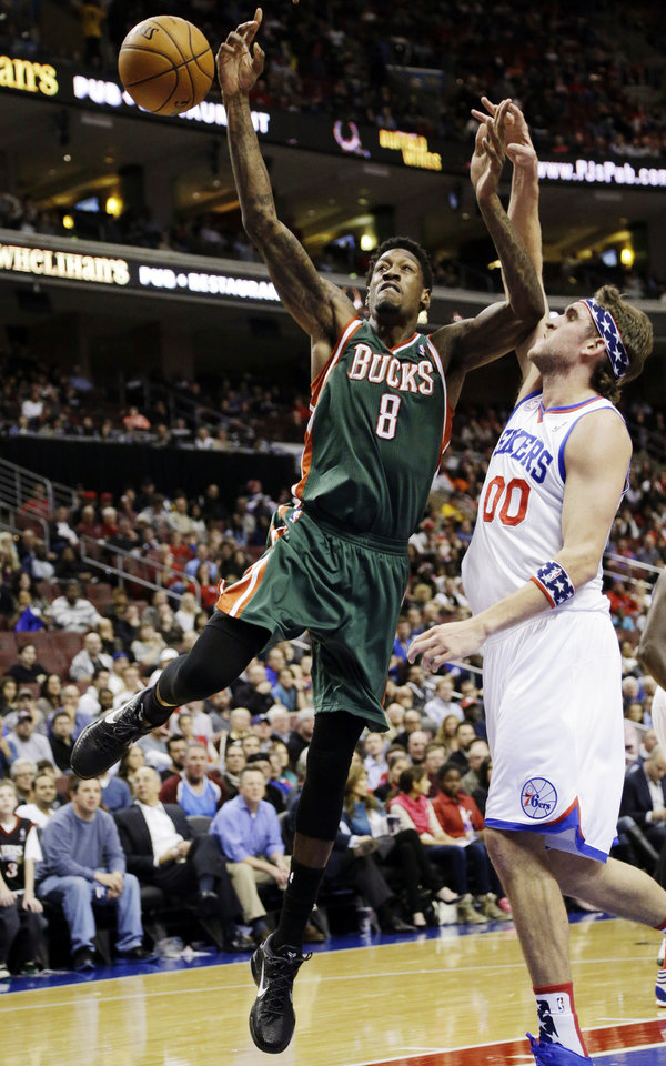 Philadelphia 76ers' Spencer Hawes (00) blocks a shot by Milwaukee Bucks' Larry Sanders (8) in the first half of an NBA basketball game, Monday, Nov. 12, 2012, in Philadelphia. (AP Photo/Matt Slocum)