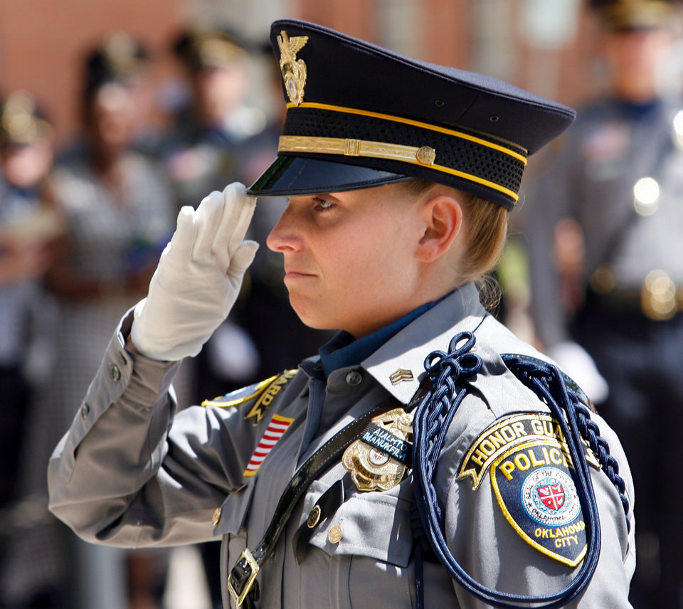 Photo - Kelly Dragus, wife Jonathan Dragus--the last Oklahoma City police officer killed in the line of duty--salutes after flowers are laid at a memorial for fallen officers in front of Oklahoma City Police Headquarters in Oklahoma City, Oklahoma on Friday, May 9, 2008.   BY STEVE SISNEY, THE OKLAHOMAN