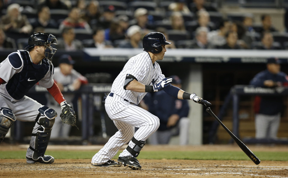Photo - New York Yankees' Jacoby Ellsbury, right, hits a fifth-inning RBI-double in a baseball game against the Boston Red Sox at Yankee Stadium in New York, Thursday, April 10, 2014. (AP Photo/Kathy Willens)