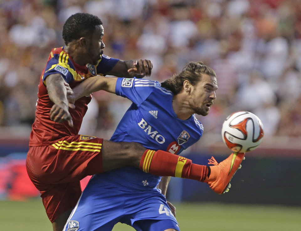 Photo - Real Salt Lake's Robbie Findley, left, kicks the ball as Montreal Impact's Heath Pearce (44) defends during the first half of an MLS soccer game on Thursday, July 24, 2014, in Sandy, Utah. (AP Photo/Rick Bowmer)