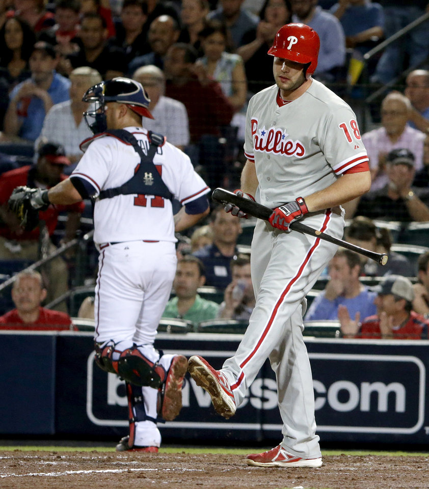 Photo - Philadelphia Phillies' Darin Ruf, right, strikes out as Atlanta Braves catcher Gerald Laird returns to the dugout in the fifth inning of a baseball game, Thursday, Sept. 26, 2013, in Atlanta. (AP Photo/David Goldman)