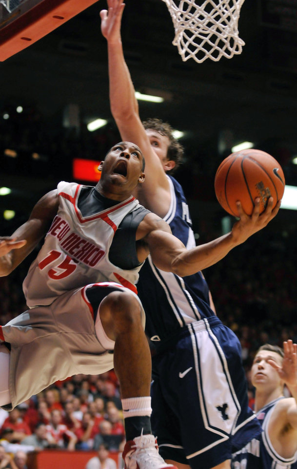 Photo - ** FILE ** University of New Mexico's J.R. Giddens, left, looks for a basket against BYU's Trent Plaisted, right, during a college basketball game in Albuquerque, N.M. in this Feb. 26, 2008, file photo. The Lobos are jockeying for a possible NCAA tournament berth one year after finishing last in the Mountain West. The team is coming off a difficult 70-69 overtime loss to BYU last week at The Pit, which snapped a six-game winning streak. (AP Photo/The Albuquerque Journal, Marla Brose, File) ORG XMIT: NMALJ101