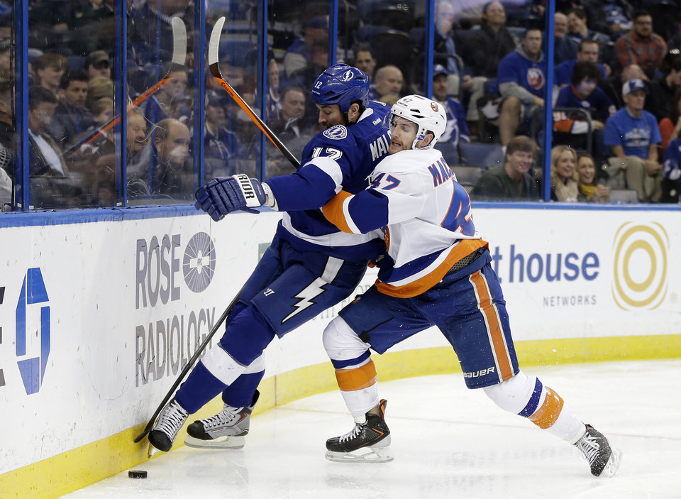 Photo - New York Islanders defenseman Andrew MacDonald (47) rides Tampa Bay Lightning left wing Ryan Malone (12) into the dasher during the second period of an NHL hockey game, Thursday, Jan. 16, 2014, in Tampa, Fla. (AP Photo/Chris O'Meara)