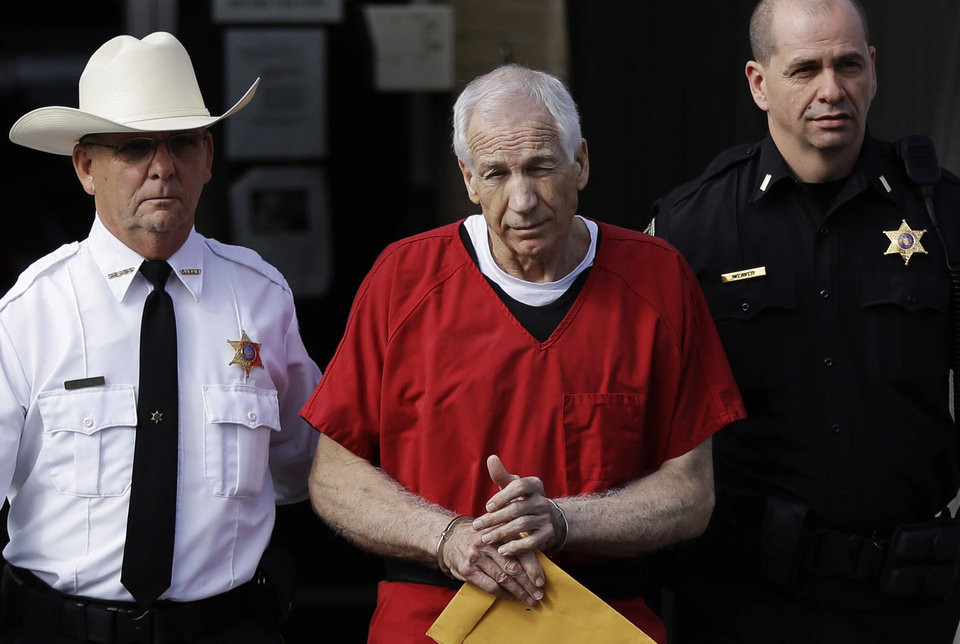 FILE - In this Oct. 9, 2012 file photo, former Penn State University assistant football coach Jerry Sandusky, center, is taken from the Centre County Courthouse by Centre County Sheriff Denny Nau, left, and a deputy, after being sentenced in Bellefonte, Pa. Seven young men, including Jerry Sandusky's adopted son, have finalized deals with Penn State over claims of abuse by the school's former assistant football coach, their lawyer said Friday, Aug. 23, 2013.    (AP Photo/Matt Rourke, File)