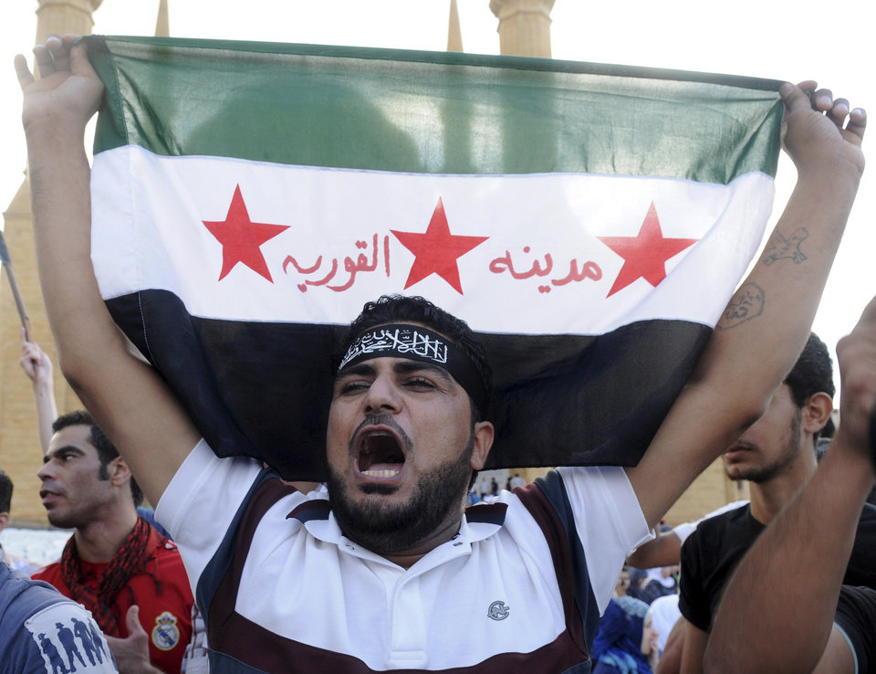 "A supporter of Sunni hard line preacher Sheikh Ahmad Assir holds up a Syrian revolution flag with Arabic that reads : ""the Syrian town of Qourieh,"" as he chants slogans during a protest  against an anti-Islam movie, in Beirut, Lebanon, Friday, Sept. 21, 2012. Anger over insults to Islam's Prophet Muhammad isn't enough to bring Lebanon's divided Sunni and Shiite Muslims together. The two sects, which have been locked in sometimes violent political competition, held separate protests Friday and even threw gibes as Sunni protesters accused Shiite Hezbollah of using the demonstrators to distract from the fighting in neighboring Syria. AP photo"