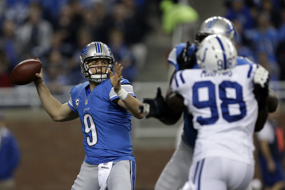 Photo - Detroit Lions quarterback Matthew Stafford (9) throws as Indianapolis Colts linebacker Robert Mathis (98) applies pressure in the first quarter of an NFL football game in Detroit, Sunday, Nov. 2, 2012. (AP Photo/Paul Sancya)