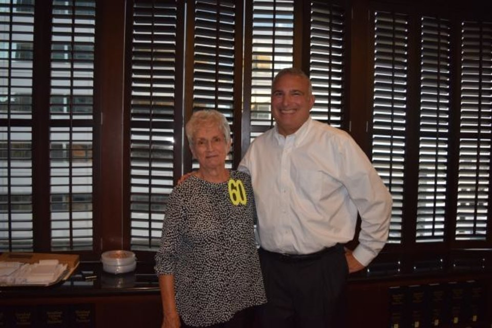 Photo -  Mike Lauderdale, managing director of McAfee & Taft law firm, congratulates Judy Webb on 60 years of service. [PHOTO PROVIDED]
