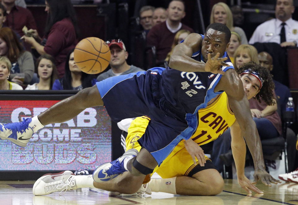 Dallas Mavericks' Elton Brand (42) flips a loose ball away from Cleveland Cavaliers' Anderson Varejao, from Brazil, in the first quarter of an NBA basketball game on Saturday, Nov. 17, 2012, in Cleveland. (AP Photo/Mark Duncan)