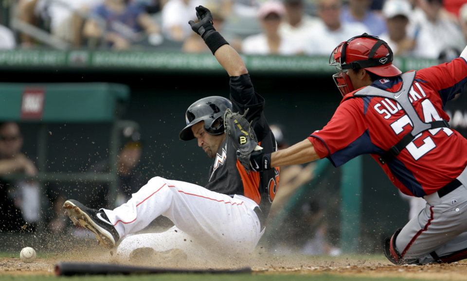 Miami Marlins' Placido Polanco, left, scores on a double by Giancarlo Stanton as Washington Nationals catcher Kurt Suzuki, right, cannot hold on to the ball during the sixth inning of an exhibition spring training baseball game Wednesday, March 20, 2013, in Jupiter, Fla. The Nationals won 7-5. (AP Photo/Jeff Roberson)