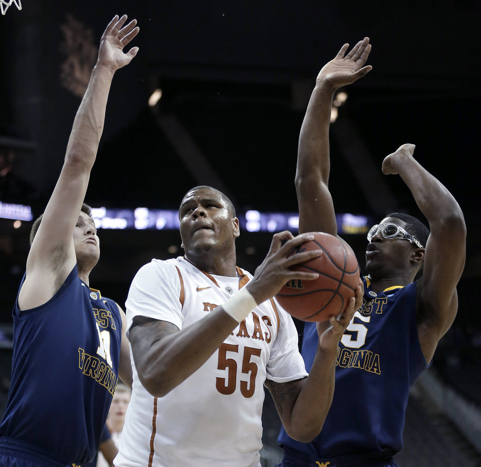 Photo - Texas' Cameron Ridley (55) looks to pass the ball under pressure from West Virginia's Nathan Adrian (11) and Devin Williams (5) during the second half of an NCAA college basketball game in the Big 12 men's tournament Thursday, March 13, 2014, in Kansas City, Mo. (AP Photo/Charlie Riedel)