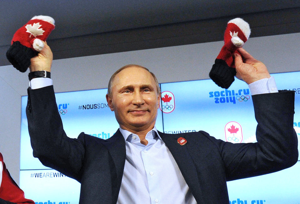 Photo - Russian President Vladimir Putin shows handmade mittens presented to him at Canada House during the 2014 Winter Olympics, Friday, Feb. 14, 2014 in Sochi, Russia. At left is Chairman of the Canadian National Olympic Committee Marcel Aubut.  (AP Photo / RIA-Novosti, Mikhail Klimentyev, Presidential Press Service)