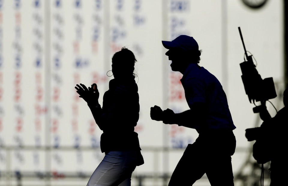 Photo - Europe's Rory McIlroy celebrates after winning the Ryder Cup PGA golf tournament Sunday, Sept. 30, 2012, at the Medinah Country Club in Medinah, Ill. (AP Photo/Chris Carlson)  ORG XMIT: PGA241