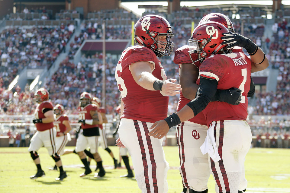 Photo - Oklahoma's Creed Humphrey (56), Tyrese Robinson (52) and Jalen Hurts (1) celebrate after a touchdown during a college football game between the University of Oklahoma Sooners (OU) and the West Virginia Mountaineers at Gaylord Family-Oklahoma Memorial Stadium in Norman, Okla, Saturday, Oct. 19, 2019. Oklahoma won 52-14. [Bryan Terry/The Oklahoman]