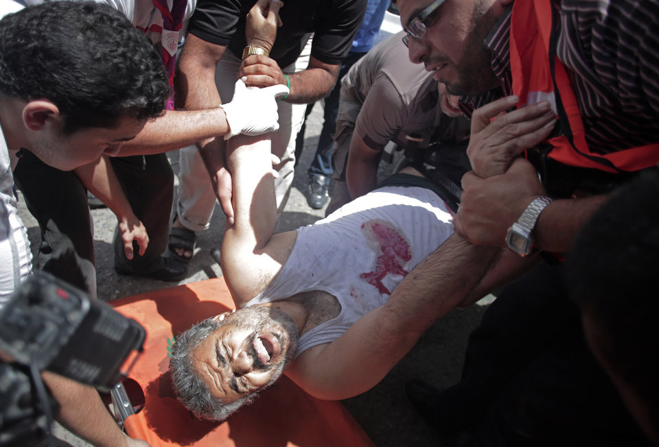 Photo - Palestinian medics place  an injured man on a stretcher in the Shifa hospital after an Israeli missile strike in Gaza City on Saturday, July 12, 2014. Palestinian officials said Israeli airstrike hit a group of people sitting in front of a closed shop killing several, raising the Palestinian death toll to more than 120 during an Israeli offensive that showed no signs of slowing down. (AP Photo/Khalil Hamra)