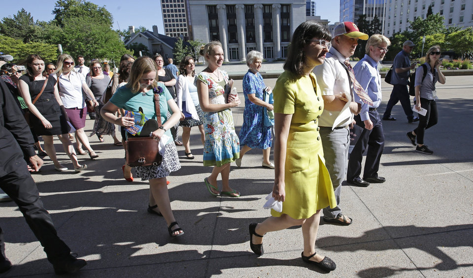 Photo - In this Sunday, June 22, 2014, photo, Kate Kelly, the founder of Ordain Women, a prominent Mormon women's group, walks with supporters to the Church Office Building of the Church of Jesus Christ of Latter-day Saints during a vigil, in Salt Lake City. Kelly could find out Monday if she will be excommunicated from her church. (AP Photo/Rick Bowmer)