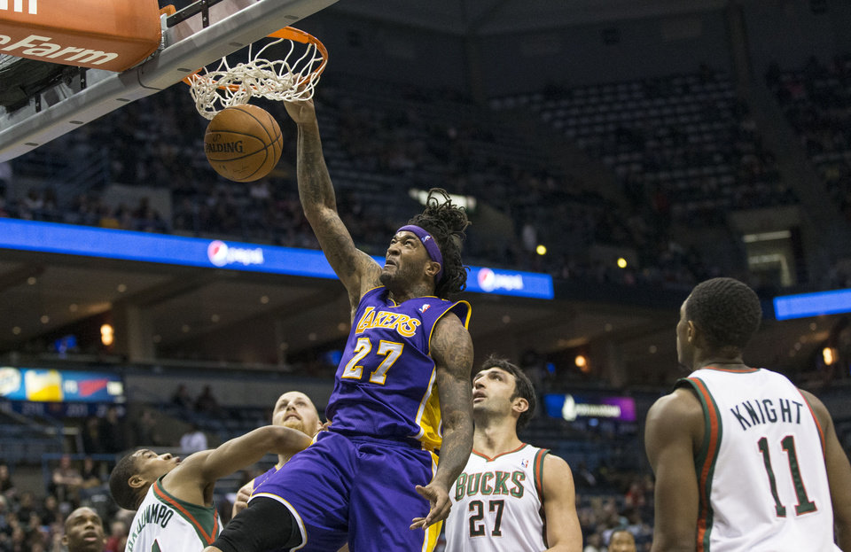 Photo - Los Angeles Lakers' Jordan Hill dunks as the Milwaukee Bucks defenders look on during the first half of an NBA basketball game Thursday, March 27, 2014, in Milwaukee. (AP Photo/Tom Lynn)