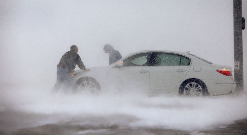 Photo - BLIZZARD / CHRISTMAS EVE / ICE / COLD / WINTER WEATHER / WINTER STORM / CAR / ASSISTANCE / SNOWSTORM / SNOW: A driver receives help after getting stuck on Britton Road in Oklahoma City Thursday, Dec. 24, 2009.  Photo by Bryan Terry, The Oklahoman ORG XMIT: KOD