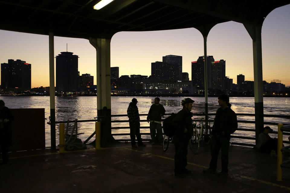 Photo - People ride the ferry boat across the Mississippi from downtown New Orleans, seen in background, to Algiers Point, Tuesday, Jan. 15, 2013. A boat ride is one of the best ways to get a look at the New Orleans skyline and the Mississippi River's daily parade of river barges, steamships and cruise ships. The Algiers Point ferry, which has been in operation since the early 1800s, is free to pedestrians.  (AP Photo/Gerald Herbert)