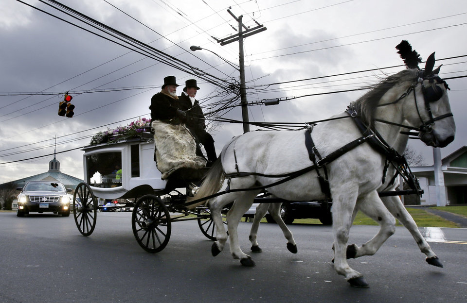 A horse drawn carriage carrying the body of Anna Grace Marquez-Greene leaves the church after her funeral in Bloomfield, Conn., Saturday, Dec. 22, 2012. Marquez-Greene, 6, was killed when gunman Adam Lanza opened fire at Sandy Hook Elementary School last week, killing 26 people, including 20 children, before killing himself. (AP Photo/Seth Wenig) ORG XMIT: CTSW113